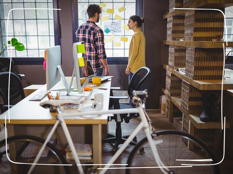 Gesunde Mitarbeiter mit Dienstfahrrad in ihrem Büro
