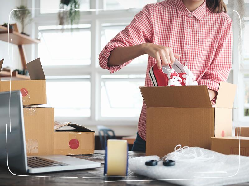 Frau packt Schuhe zum Verkaufen in Karton